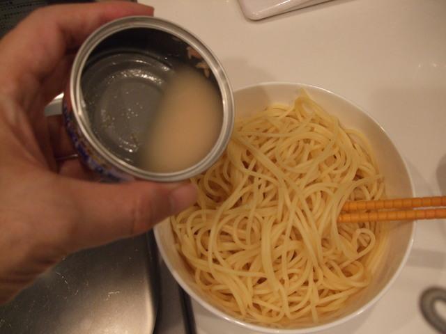 茹でたパスタ麺にツナ缶の油をまぶそうとしているところ